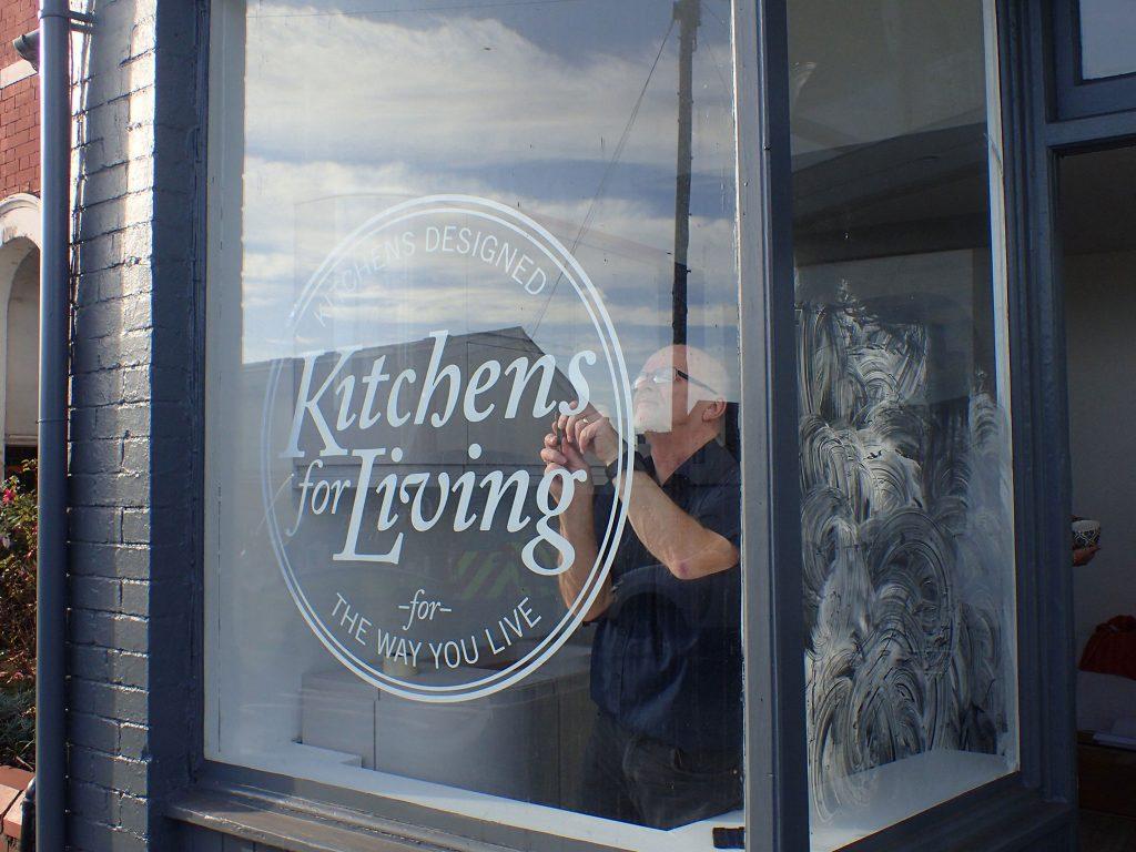 Man installing vinyl sticker in shop window